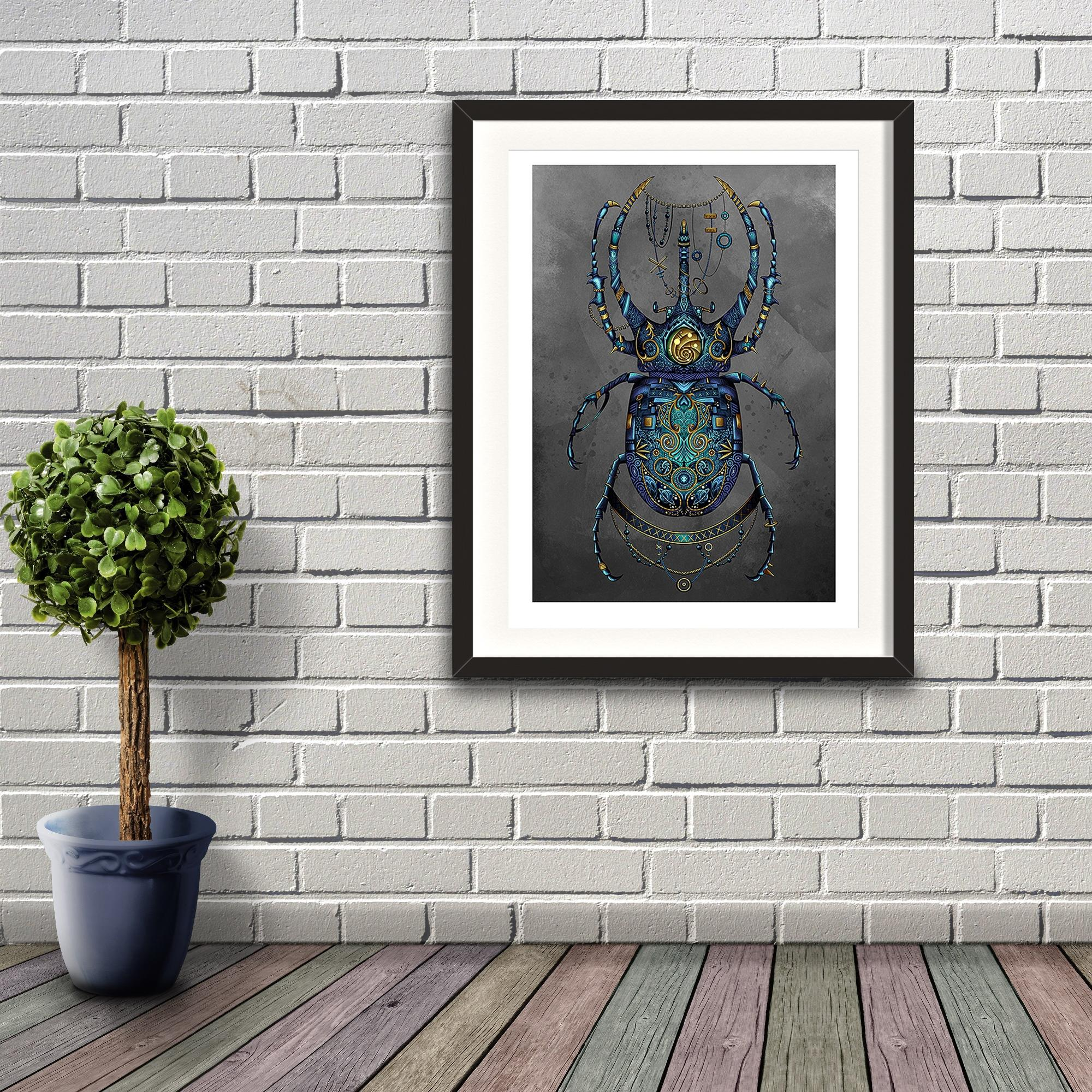 A digital painting by Lily Bourne printed on eco fine art paper titled Beetle showing a jewel encrusted beetle coloured blue and turquoise with grey background in a steam punk style. Print shown hanging on a brick wall.
