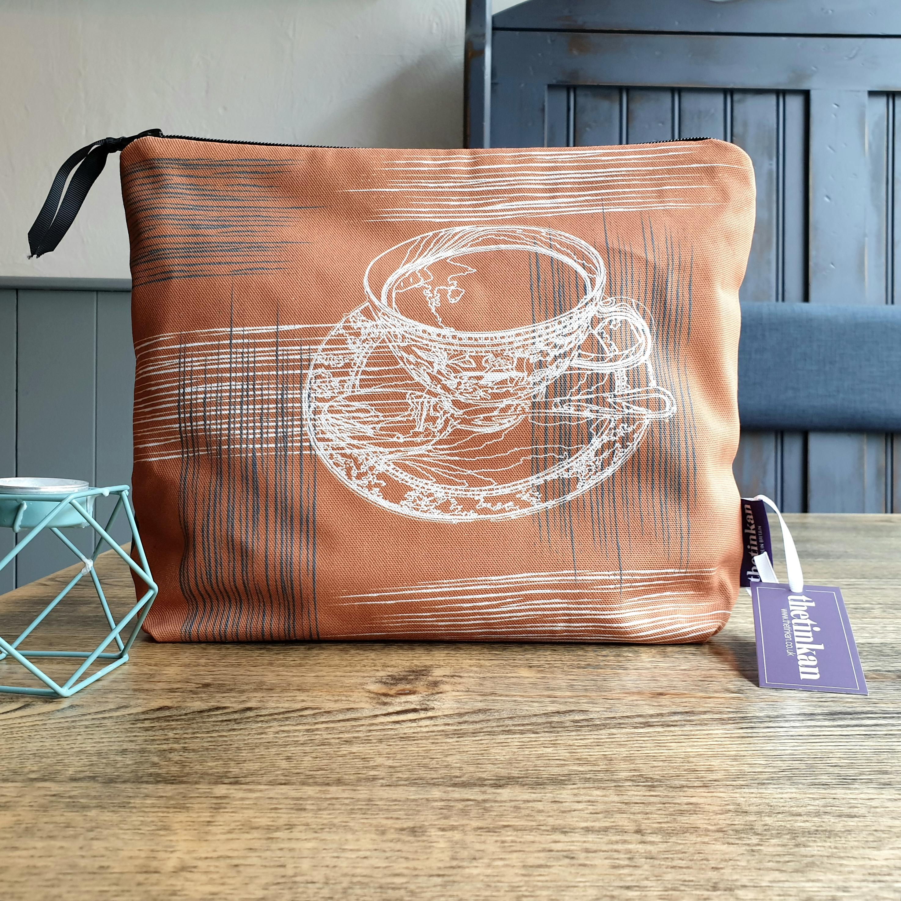 Warm rust orange with grey coloured reverse, travel beauty washbag featuring the white traced outline of a classic British teacup & saucer. Made from panama cotton with black waterproof lining and matching black sturdy zip. Generously sized for all your travel or home needs. Designed by thetinkan. VIEW PRODUCT >>
