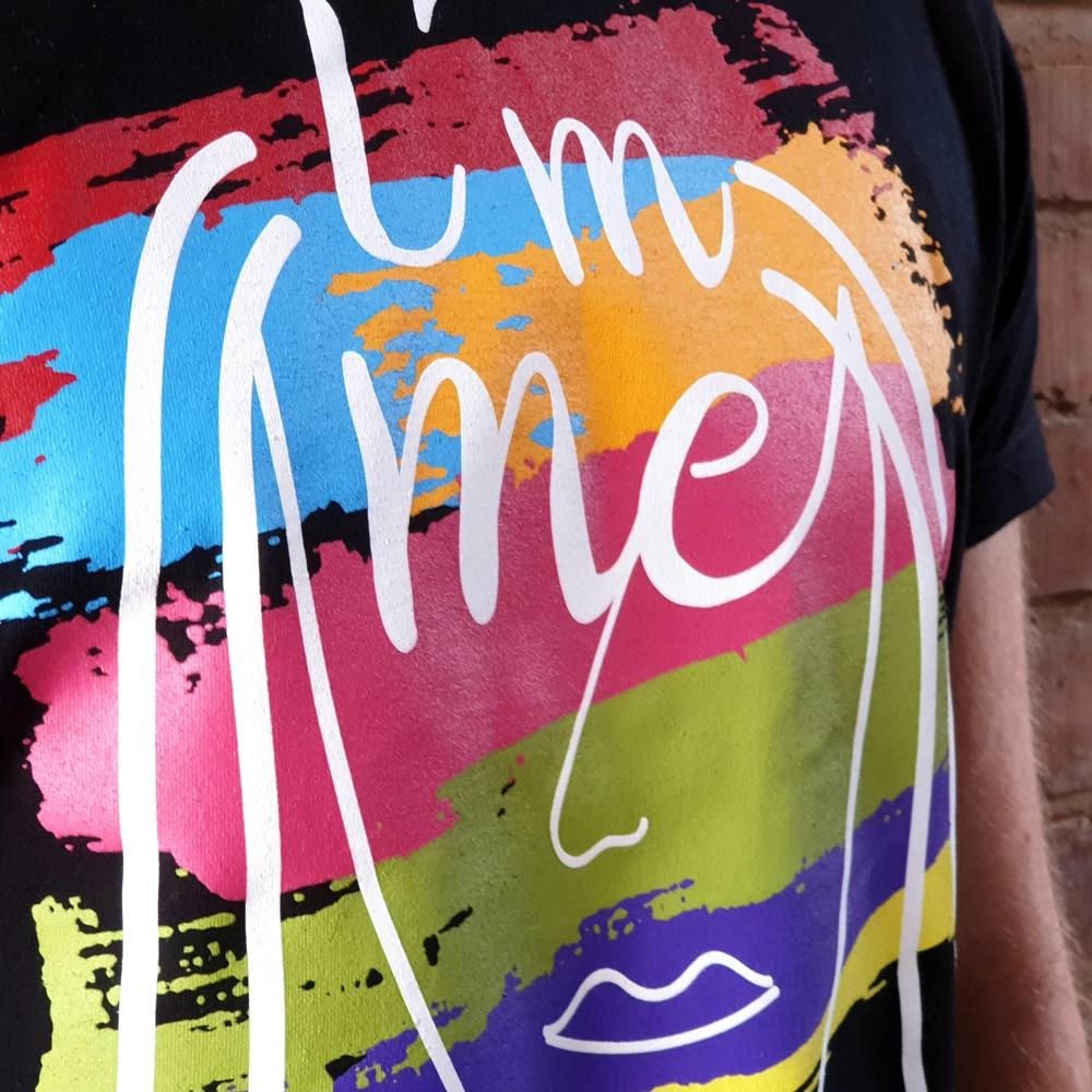 Close up photo of black t-shirt with white handdrawn face and rainbow painted stripes with the words I'm Me & Proud printed. Designed by thetinkan. VIEW PRODUCT >>