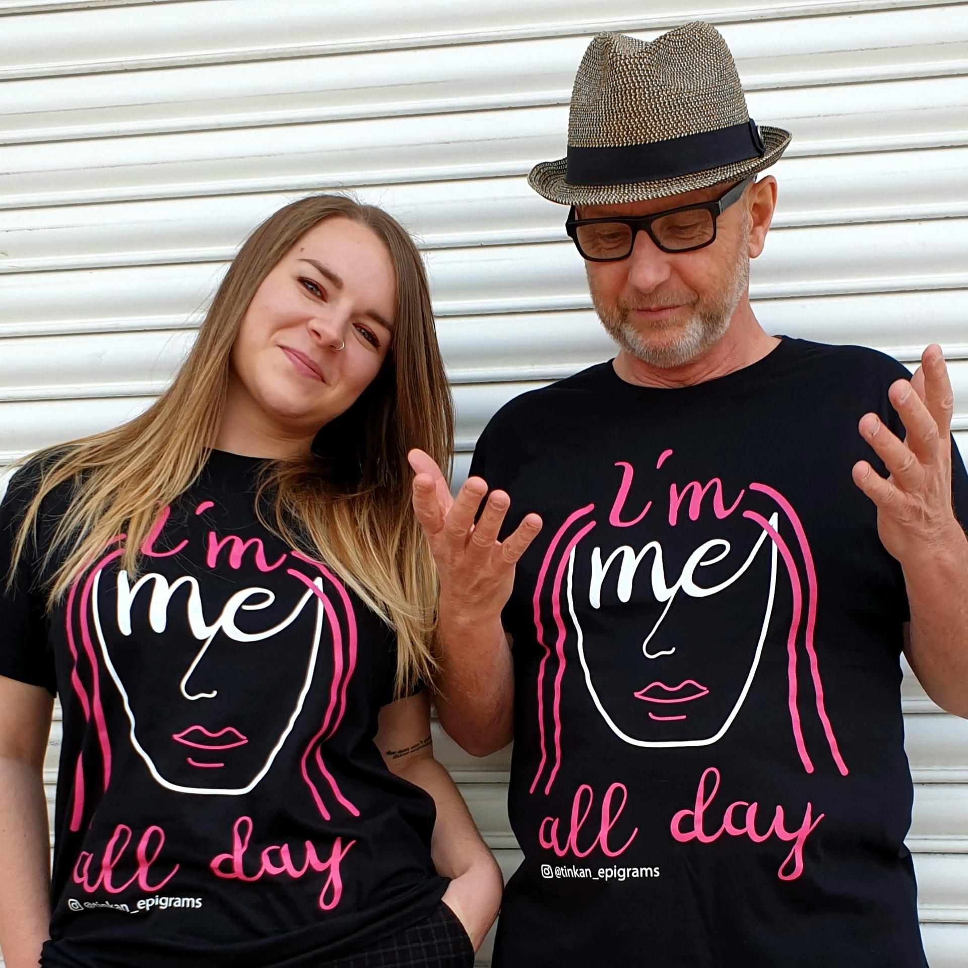 Adult female and male wearing black t-shirt with white handdrawn face with pink hair with the words I'm Me All Day printed. Designed by thetinkan. VIEW PRODUCT >>