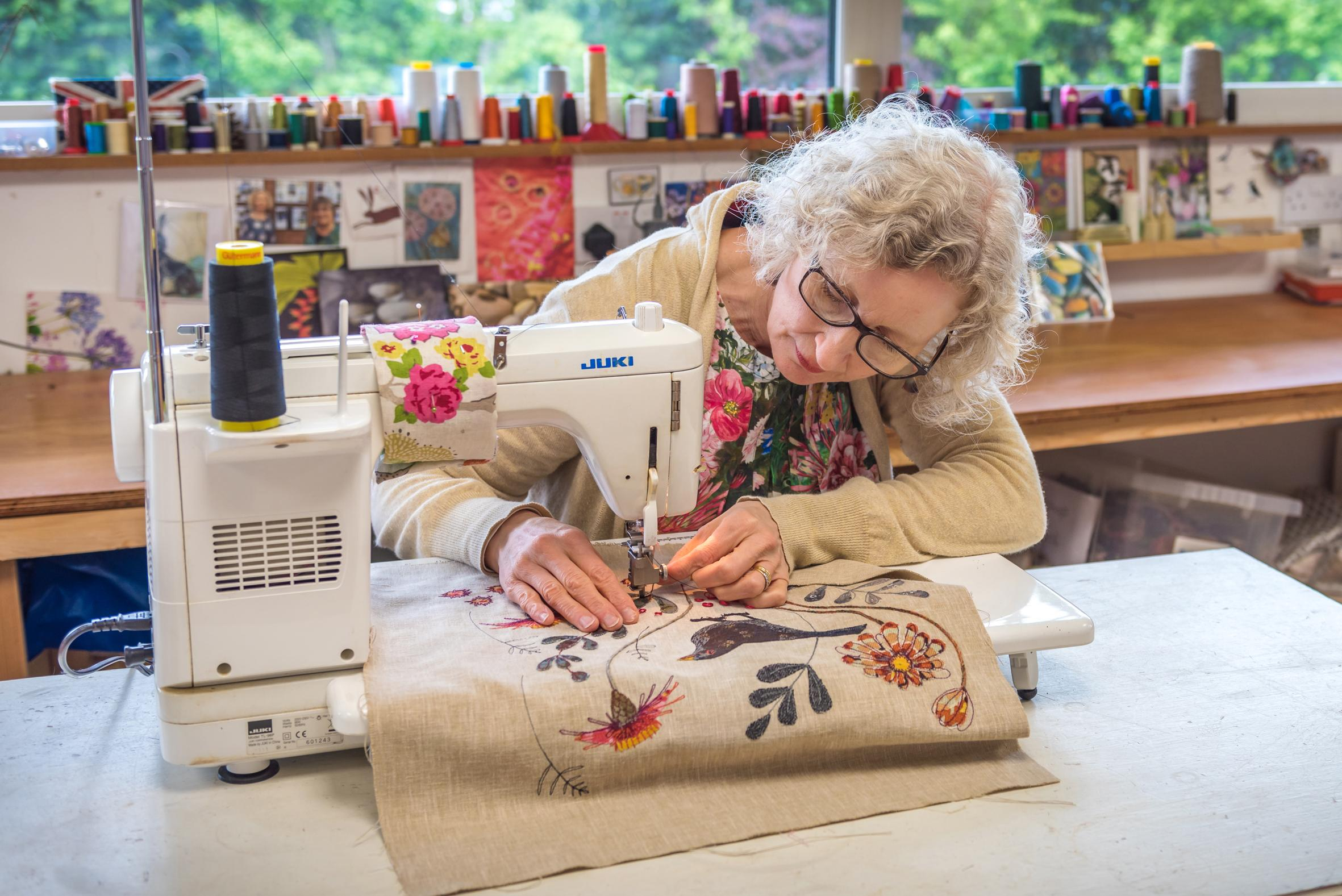 Jo Hill sewing on her machine in her garden studio
