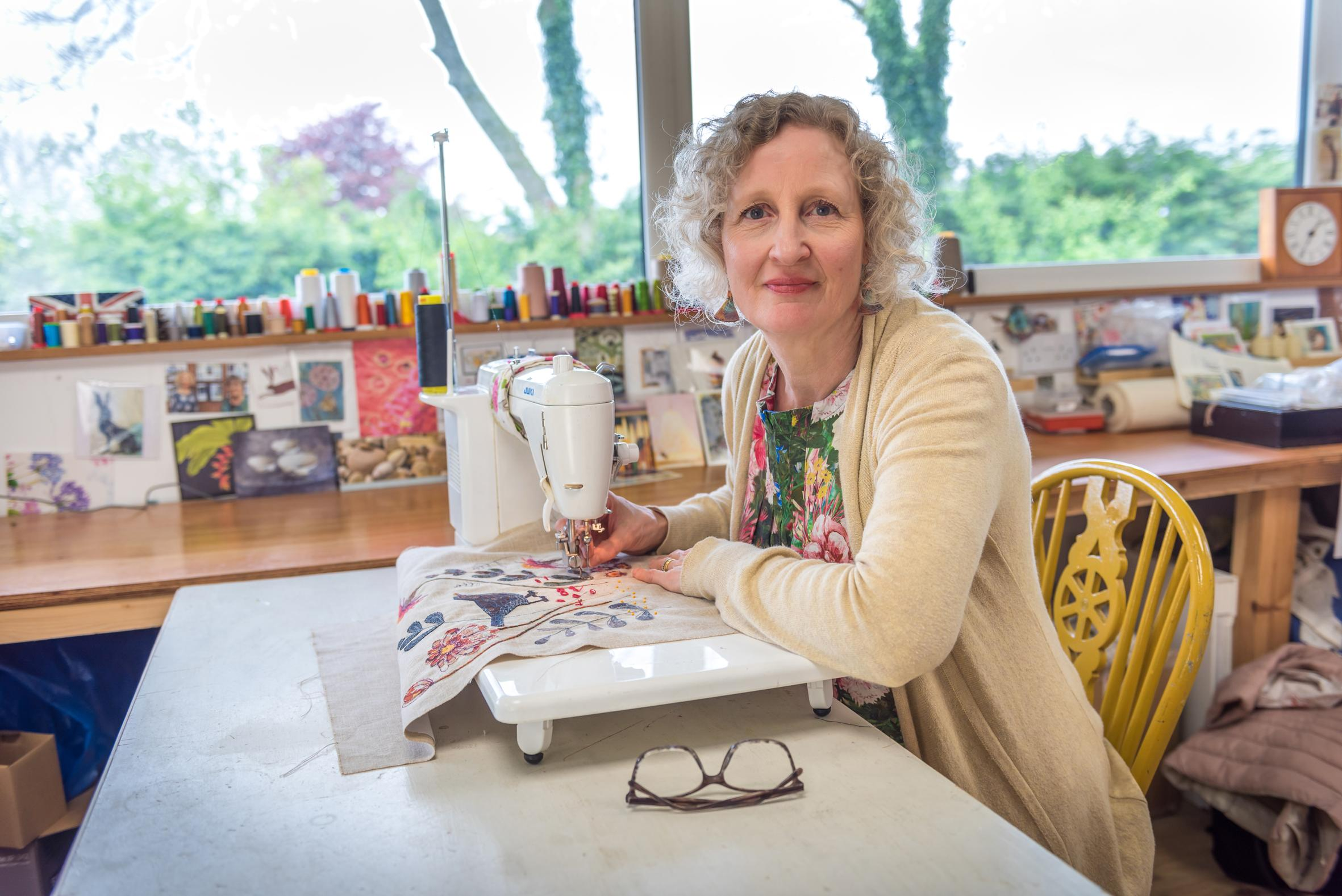 Jo Hill at her sewing machine, stitching a blackbird design and smiling at the camera