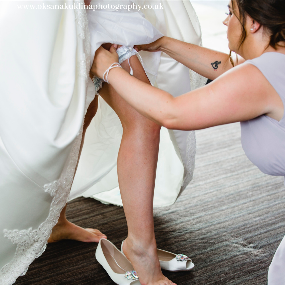 Matron of honour helping the bride with her wedding garter