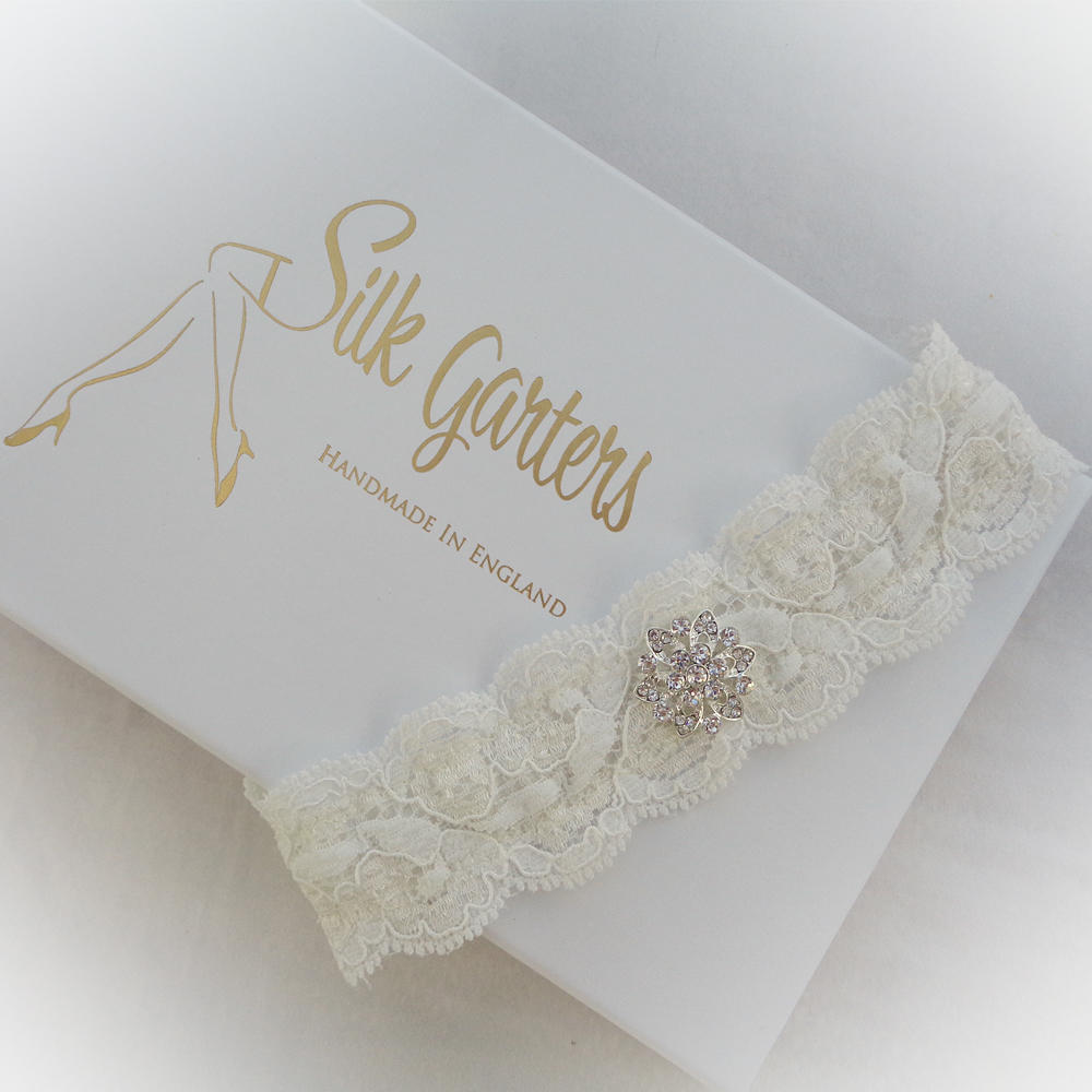 Flat lace wedding garter in ivory with a simple crystal