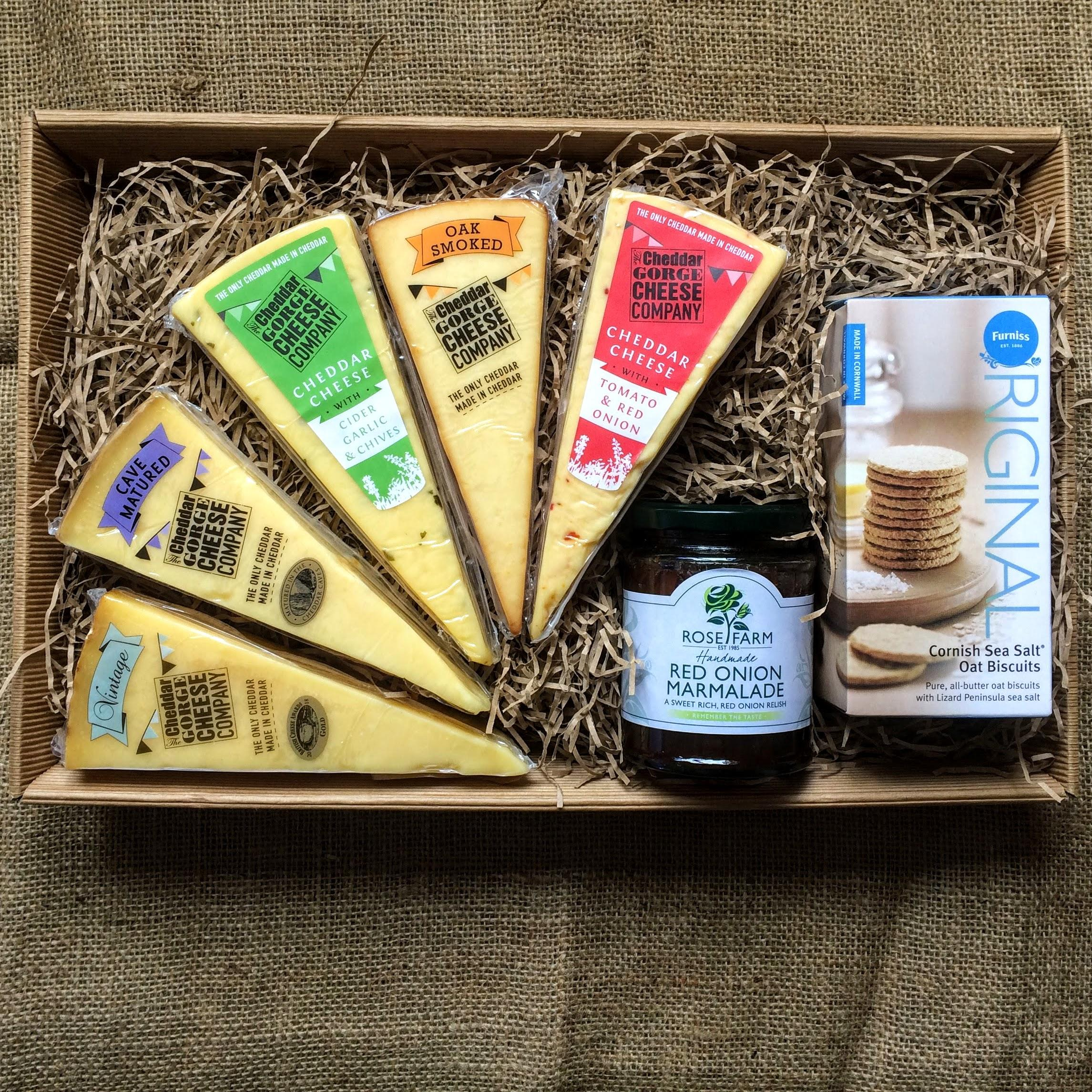 A decorative cardbaord tray containing five portions of premium cheddar, a jar of relish and a pack of Cornish Sea Salt biscuits.