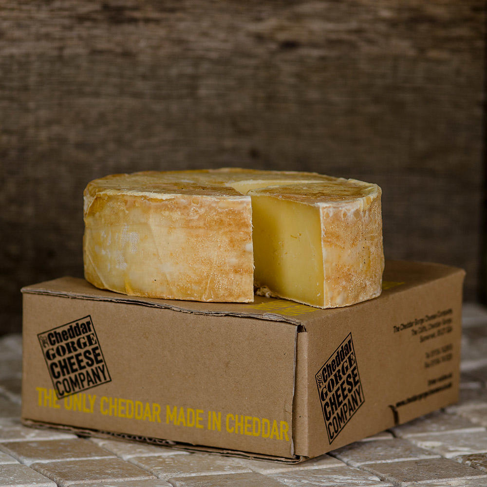 A small truckle of cheddar cheese on top of a box