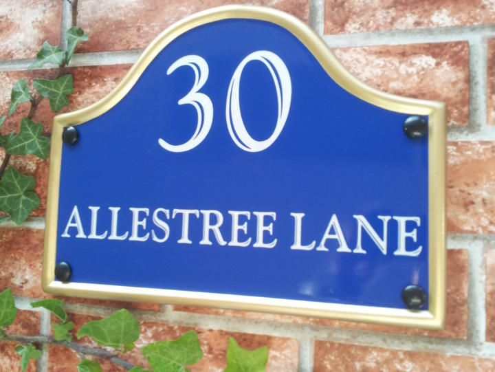 House plaque with number and address line in blue with a gold rim