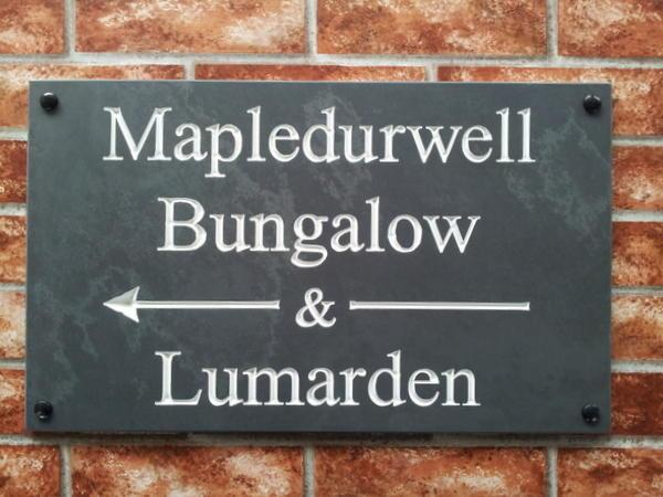 Large slate directional sign with arrow