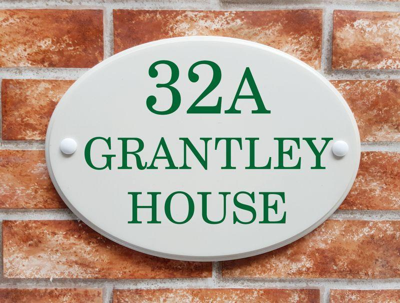White address sign with green house name