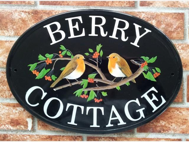 Two robins on branch sign