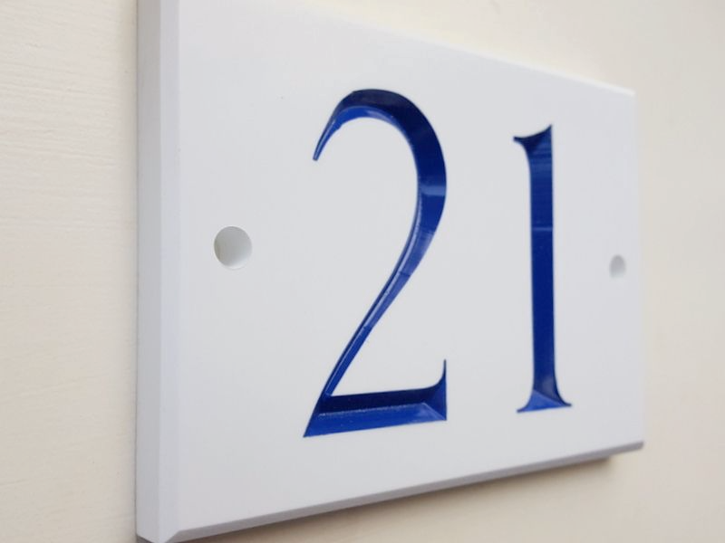 White door number in Toledo font with a blue inlay