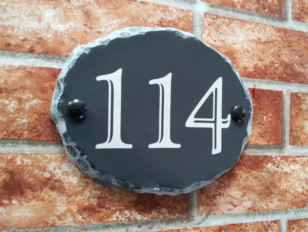 Oval house number plaque with 114 and rustic edges