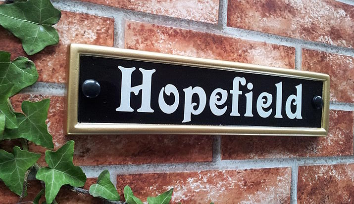 House name plaque in black with a gold rim displaying Hopefield