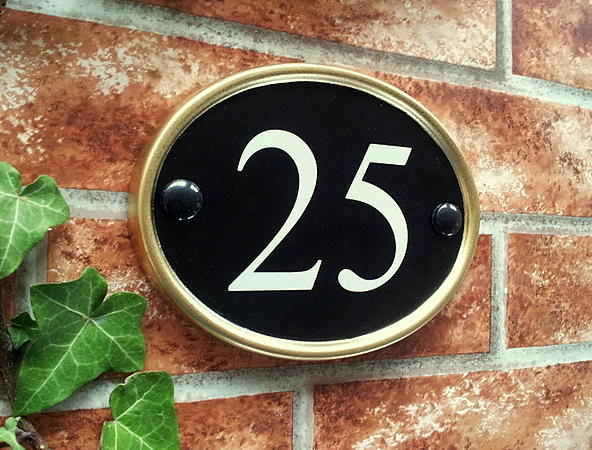 Oval number sign in black with a gold rim and number 25