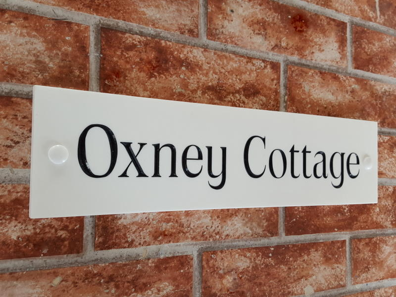 White house name plate with Oxney Cottage