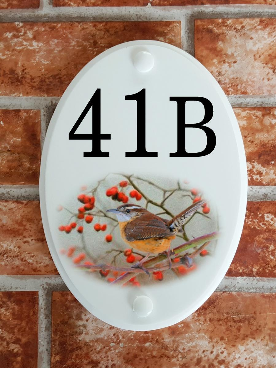 House number plate displaying a wren bird among red berrirs