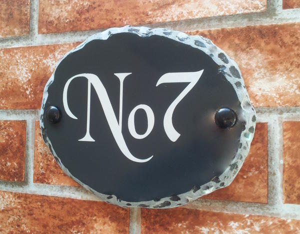 Oval house number in rustic style with No. 7