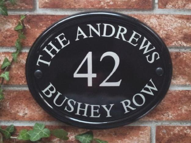 Oval sign in black with house name, number and address line
