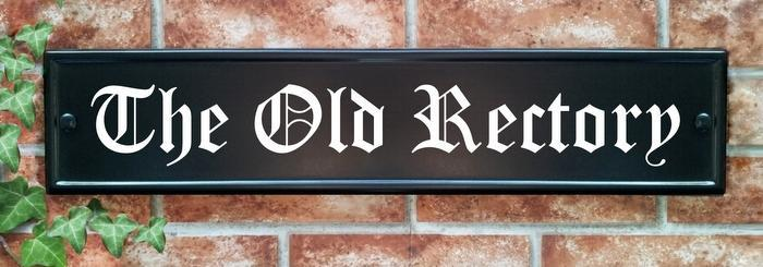 Large black house name sign with night reflective text