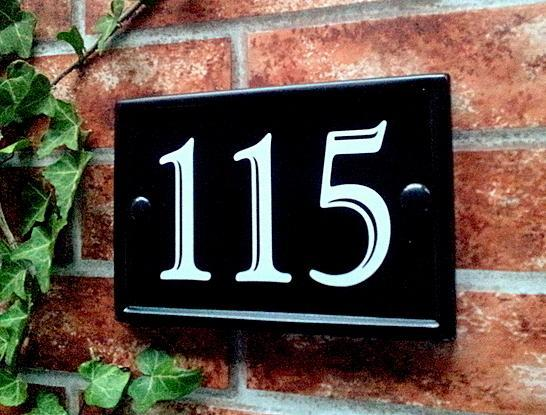 Black rectangular plaque with number 115