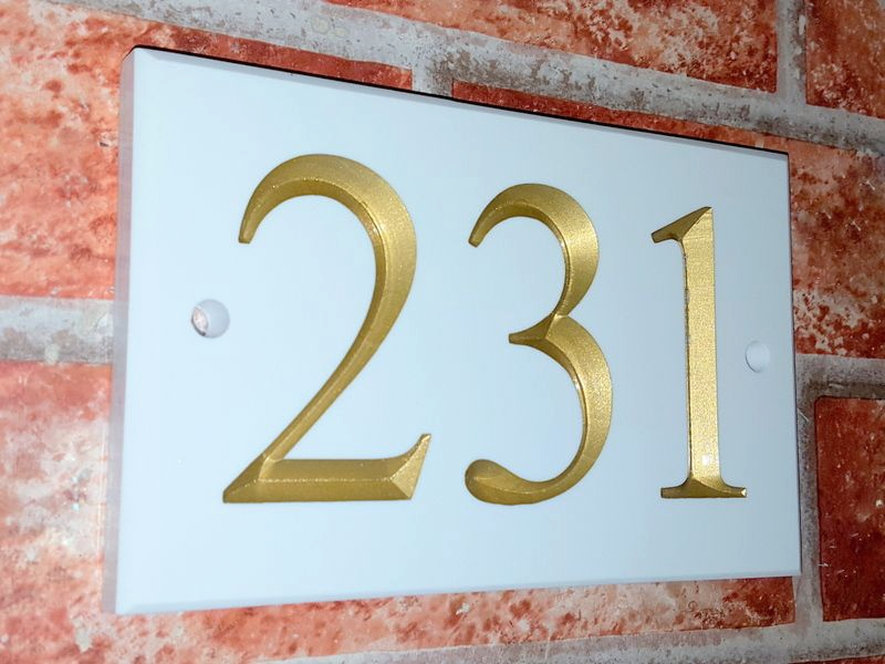 White sign displaying number 231 with a gold inlay