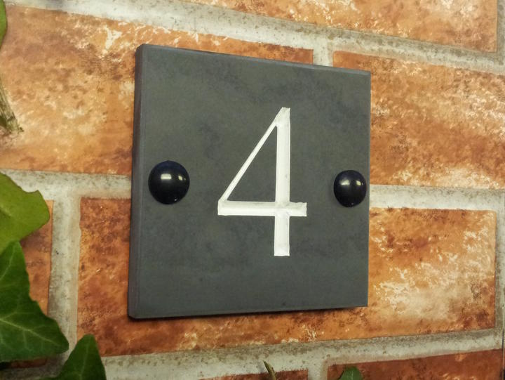 Slate house number sign displaying a 4 with white inlay