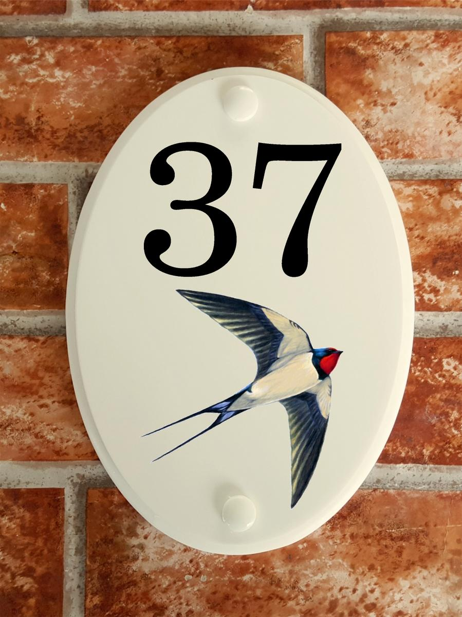 House number plate with a swallow picture motif