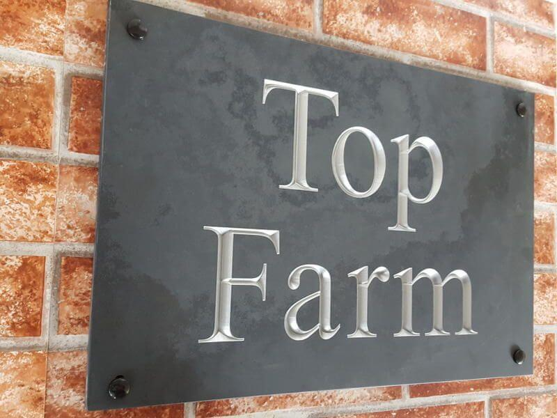 engraved slate house sign with silver text