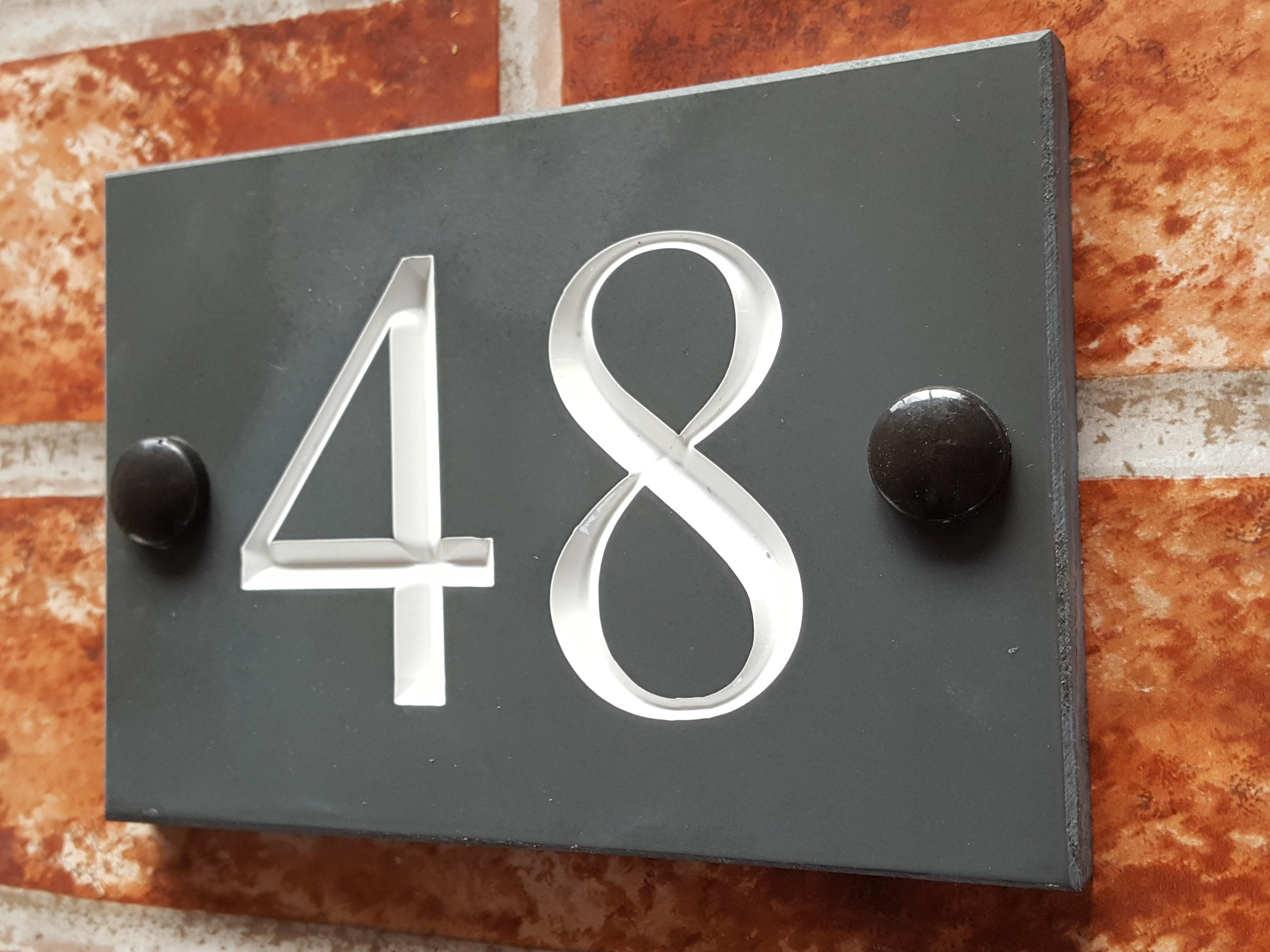 Budget house number plate displaying 48 in white times roman font
