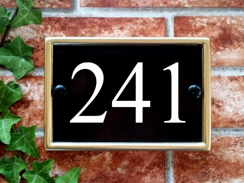 Rectangular house number sign in black with a gold rim