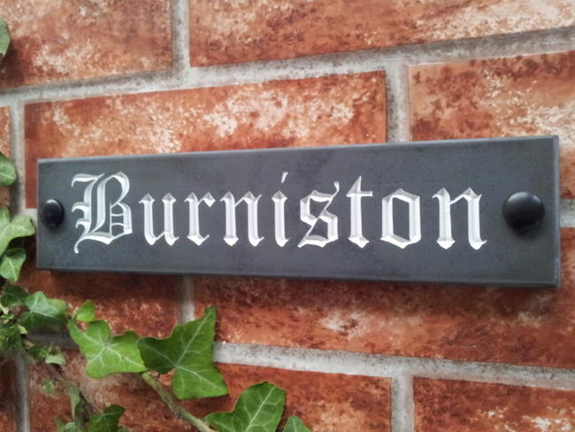 Slate sign displaying Burniston with white inlay