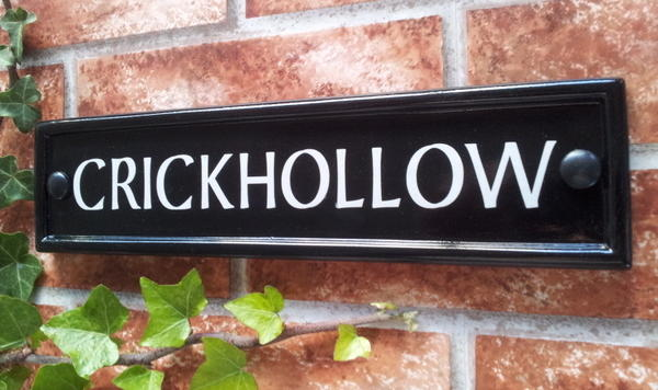 Black rectangular house name sign with Crickhollow