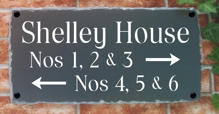 Large directional sign with house name, numbers and arrows