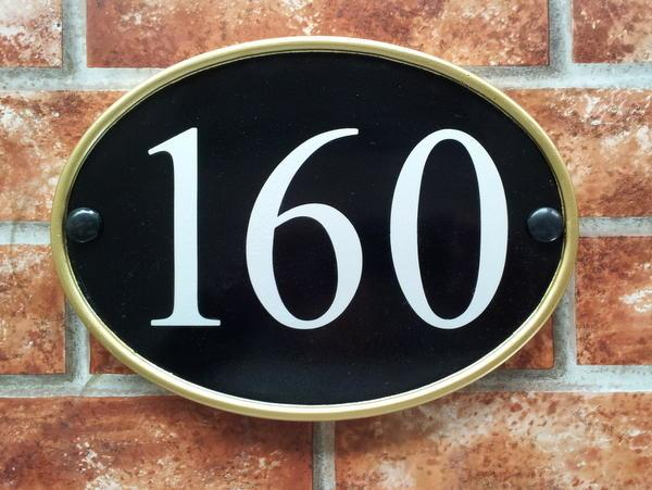 Large house number sign in black with gold rim and 160