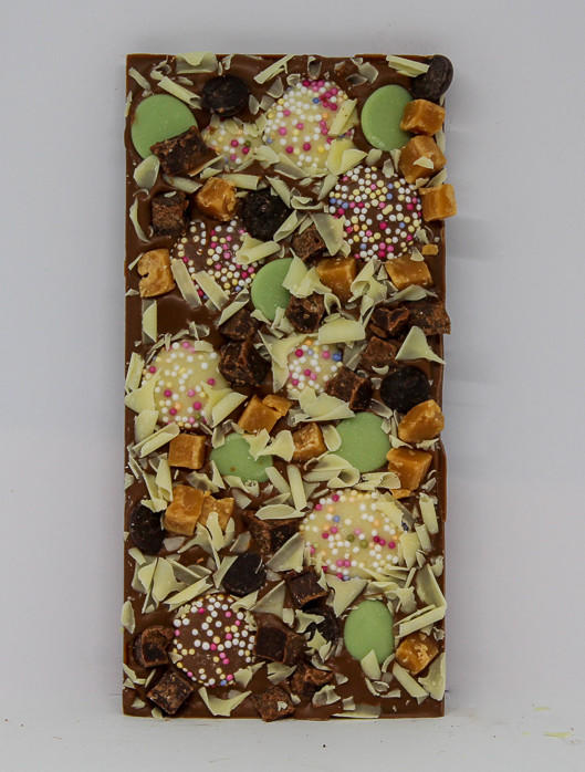 34% milk chocolate with milk and white chocolate jazzies, lemon flavour buttons, dark chocolate buttons, caramel fudge, fudge brownie pieces and white chocolate curls