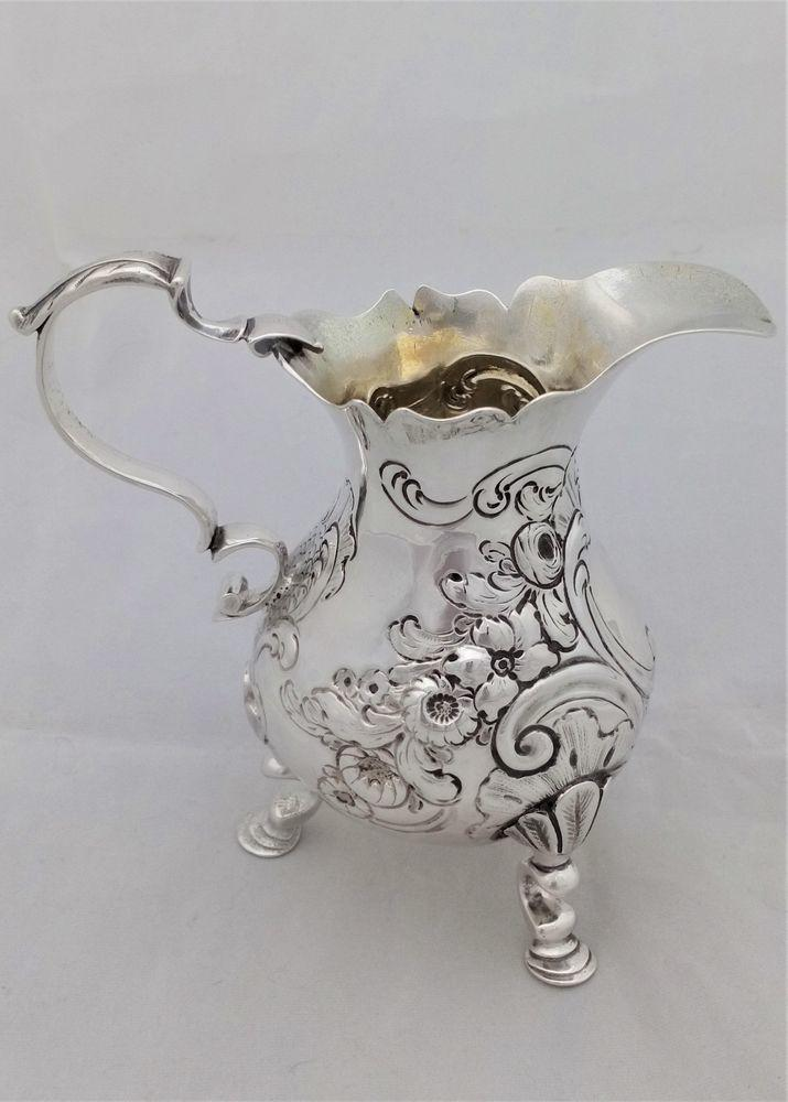 Antique George II silver cream jug, pear shaped repousse decorated body on three scroll pad feet. Hallmarked Sterling silver London 1753 made by Louis Hamon weighs approximately 101 grammes.