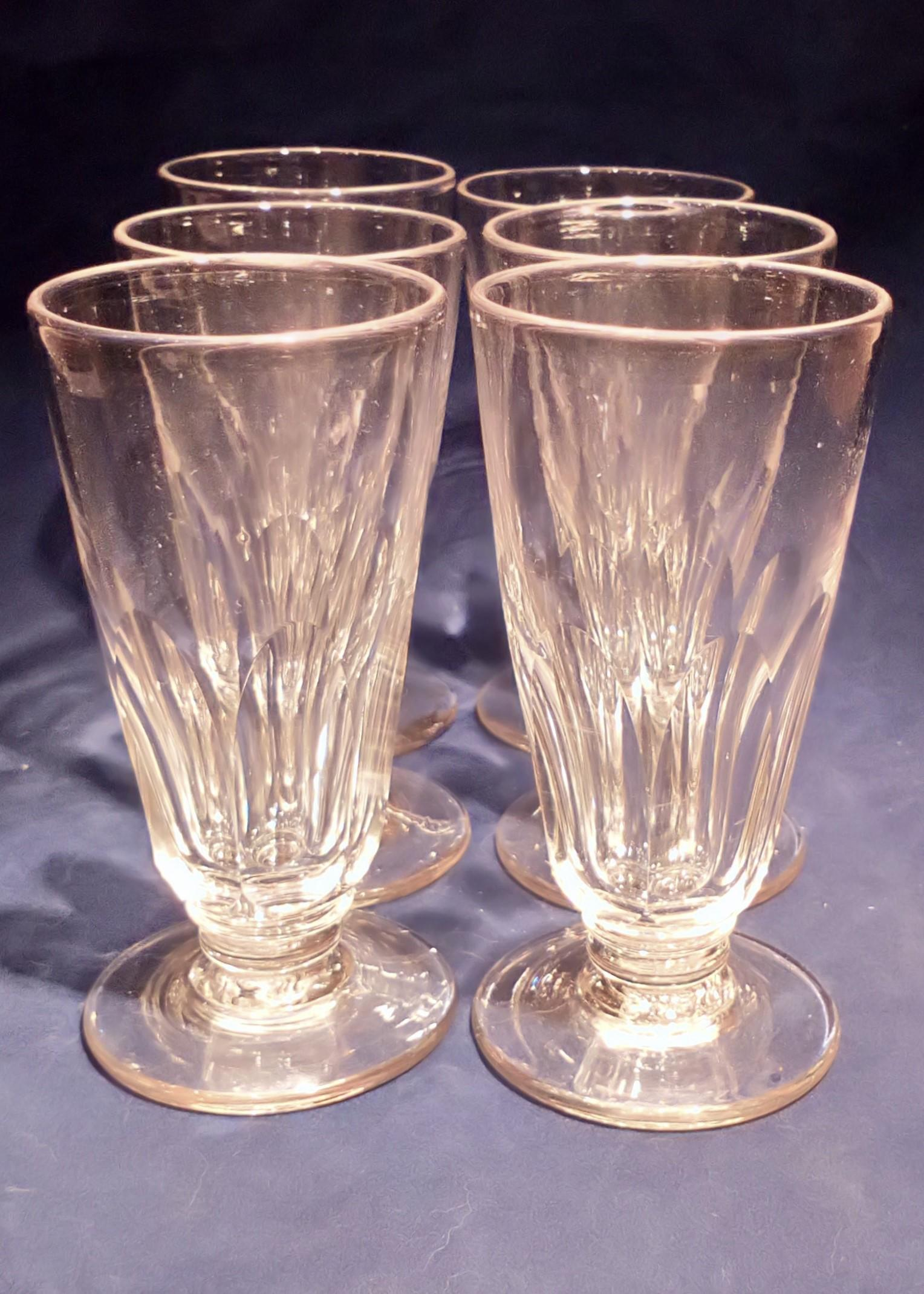 Set of six antique faceted trumpet bowled aperitif glasses with blade knop rudimentary stem and low moulded foot French 19th C