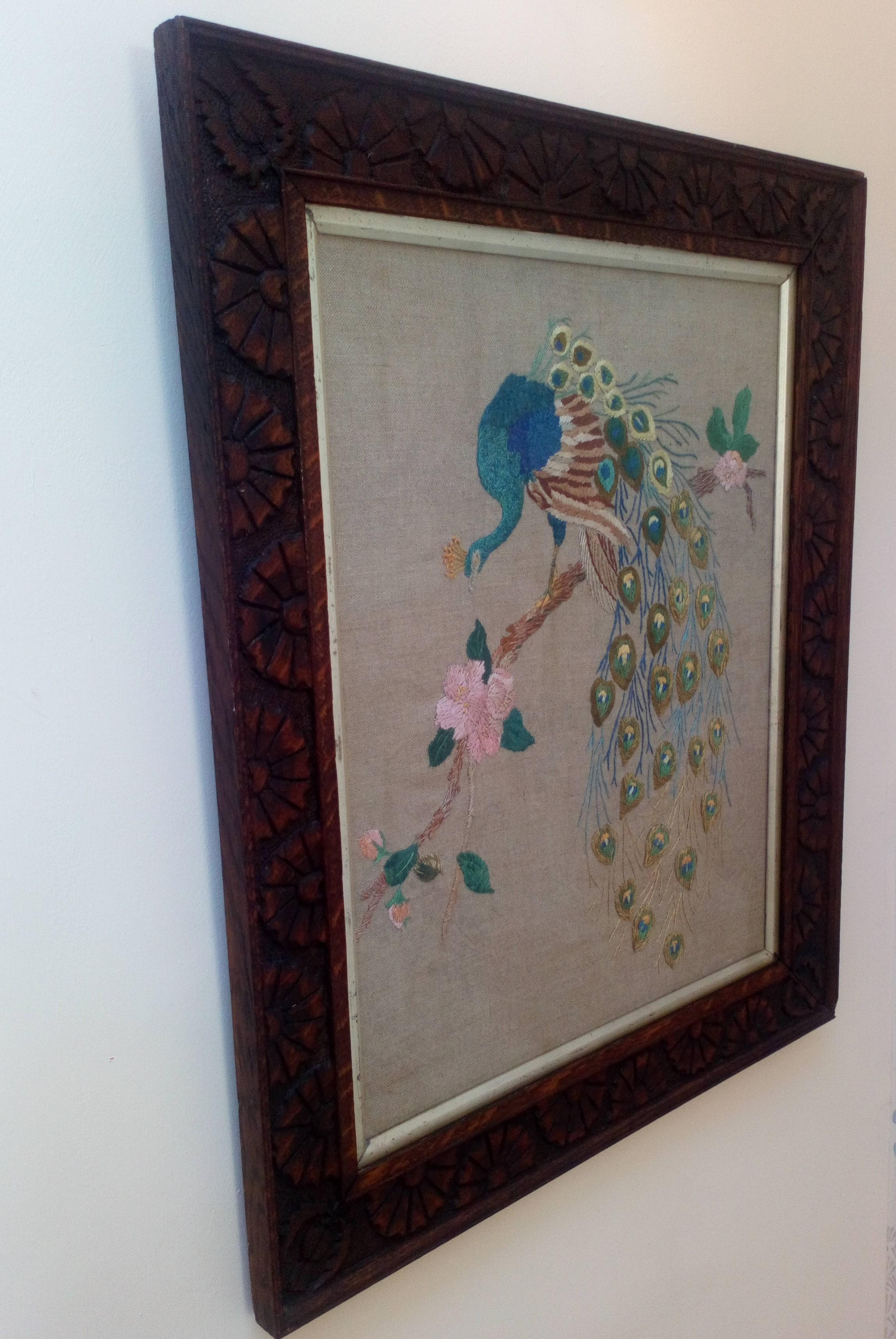 Antique Arts and Crafts Peacock silk long stitch embroidery on unbleached linen in a thistle and daisy carved oak wooden frame