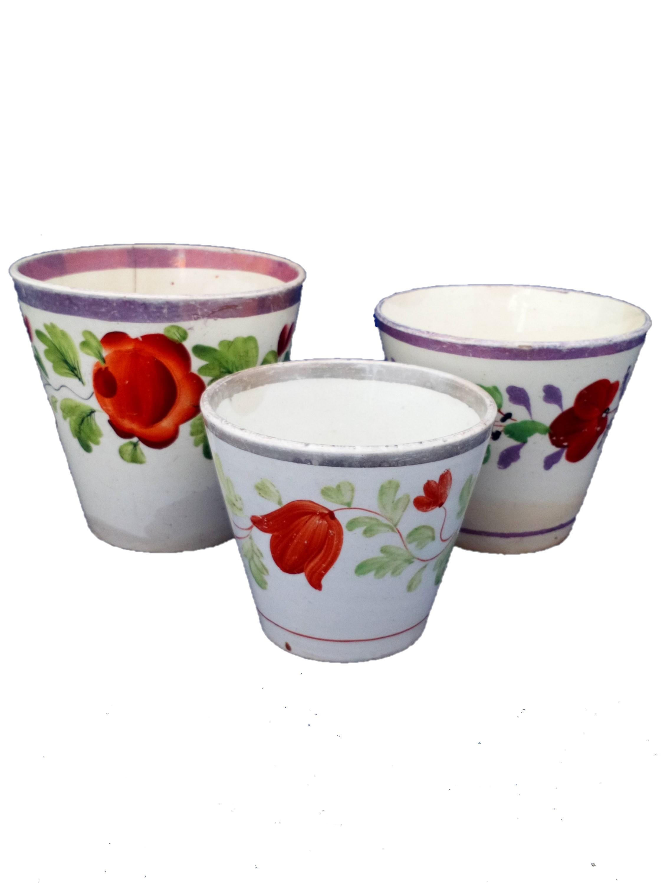 Three antique graduated pearlware and creamware pottery pink lustre ale beakers or cups with hand painted flowers circa 1820