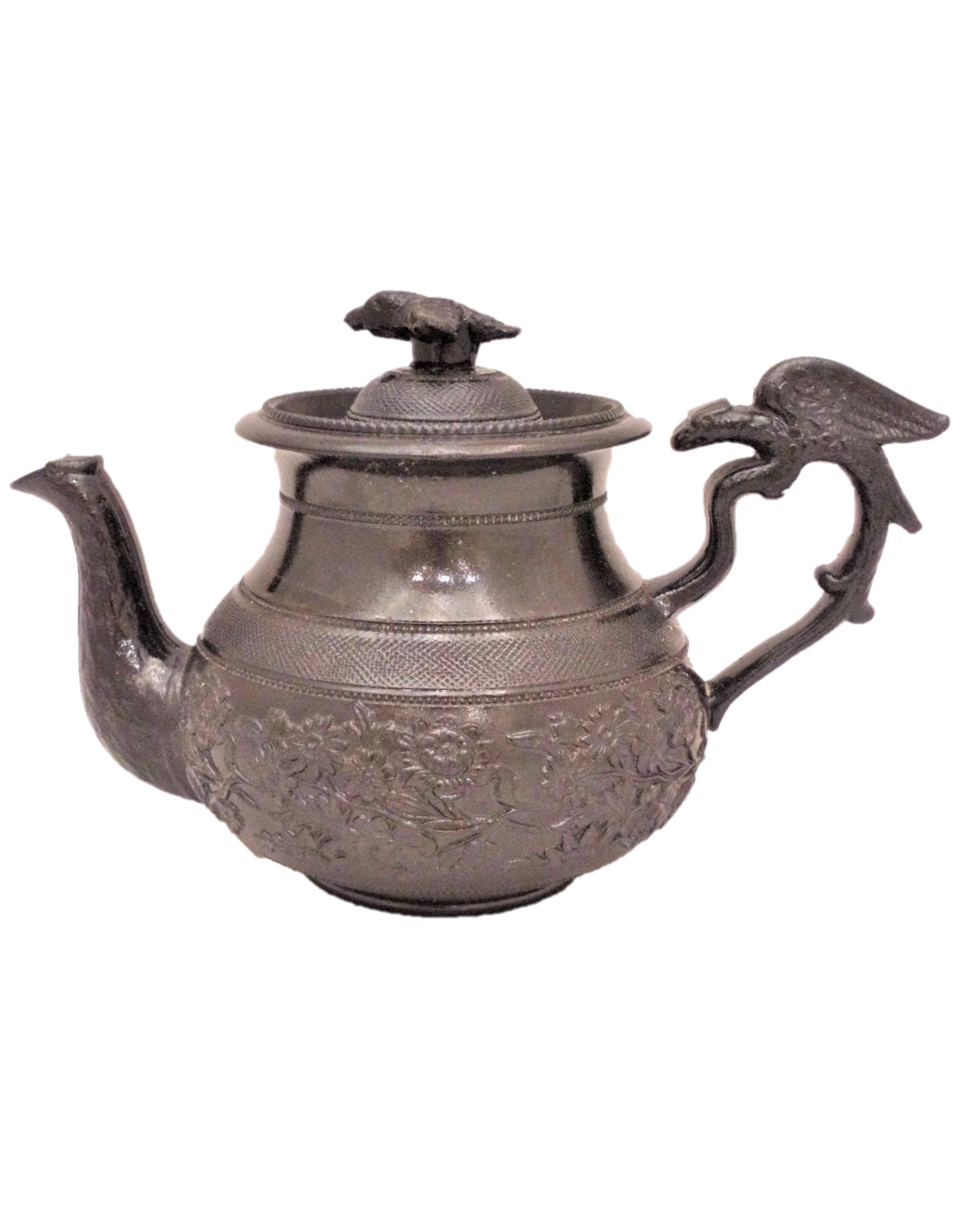 An antique Cyples Egyptian black floral sprigged baluster shaped glazed basalt teapot with an eagle handle and bird finial circa 1830