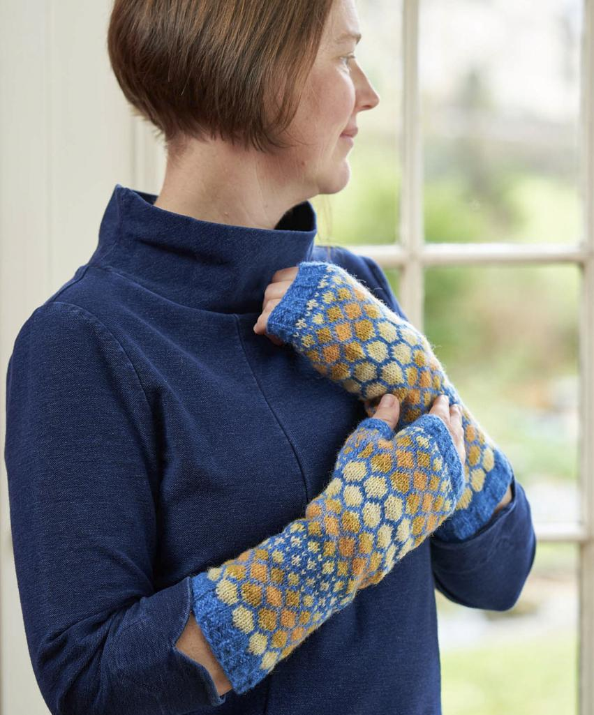 Skystone Armwarmers in sky-inspired colours, modelled by Jen who wears them with a dark blue dress and looks out of the window.