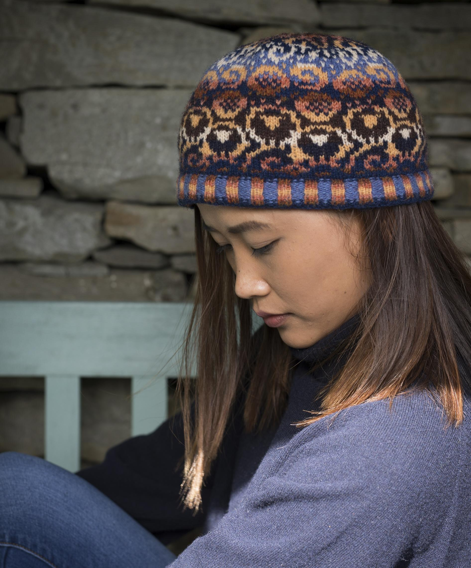 A model who appears to be of Asian heritage sits on a bench and looks down and to the side while wearing a brightly-patterned stranded colourwork hat bearing motifs of sheep, glyphs, waves and moons, in a palette of corals, golden shades and deep warm blues and browns