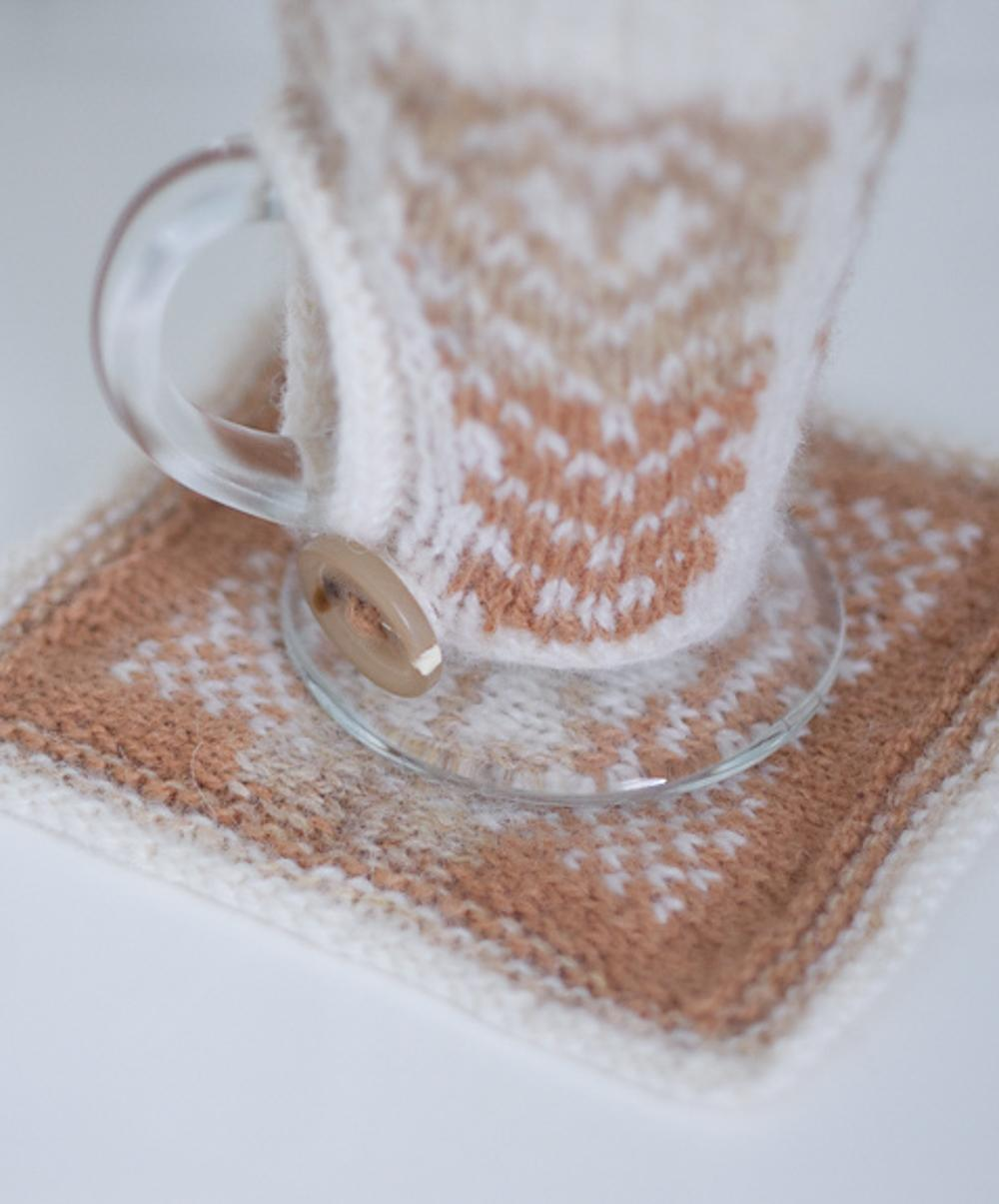 Latte glass covered in latte-art inspired stranded colourwork woolly cosy, with matching woolly coaster.