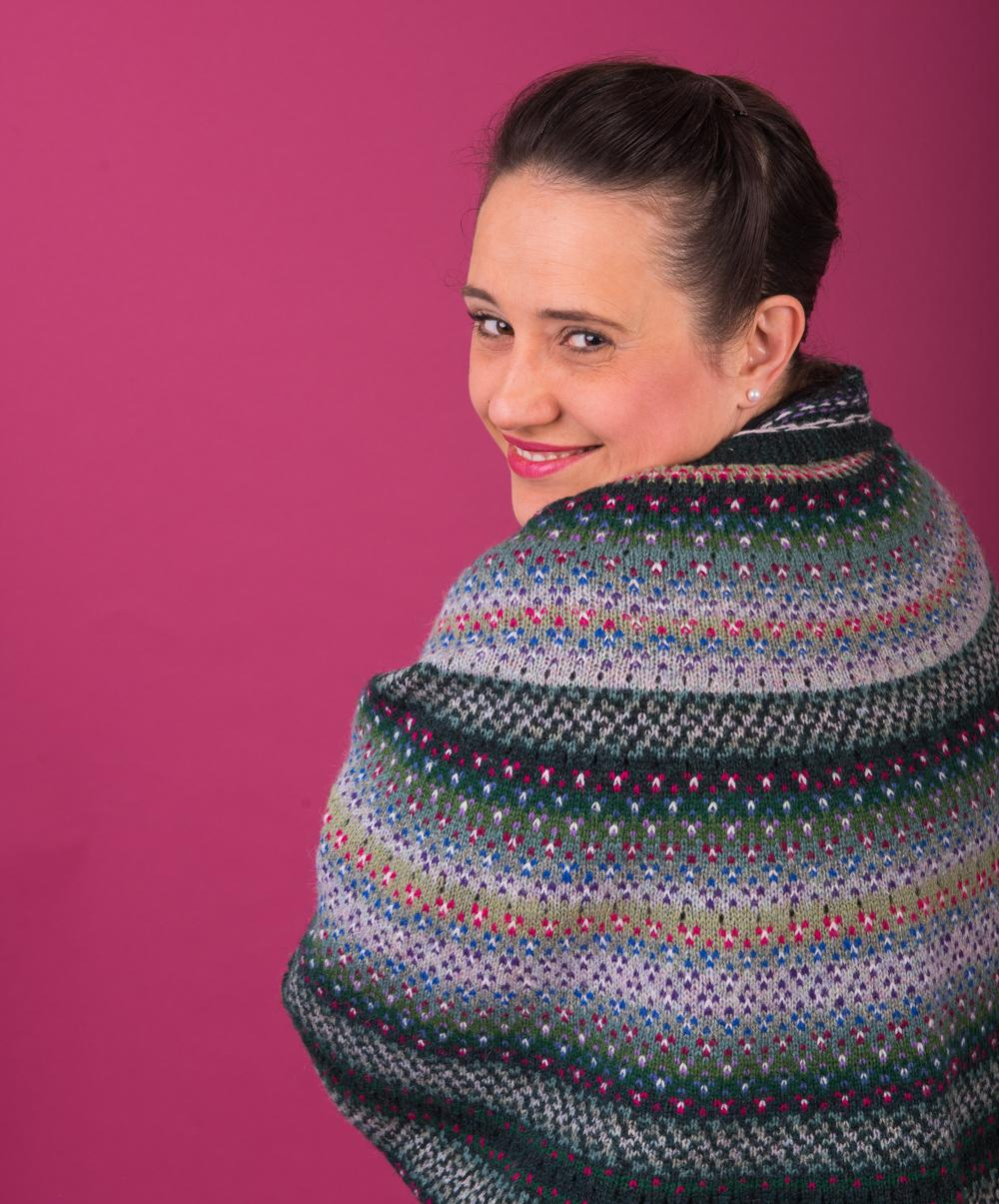 Judith wears the Efflorescent Shawl from KNITSONIK Stranded Colourwork Playbook