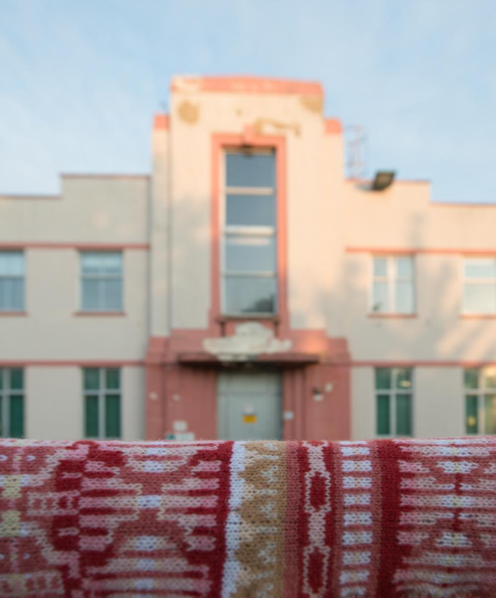 Pink art-deco style factory building presented alongside knitted interpretation