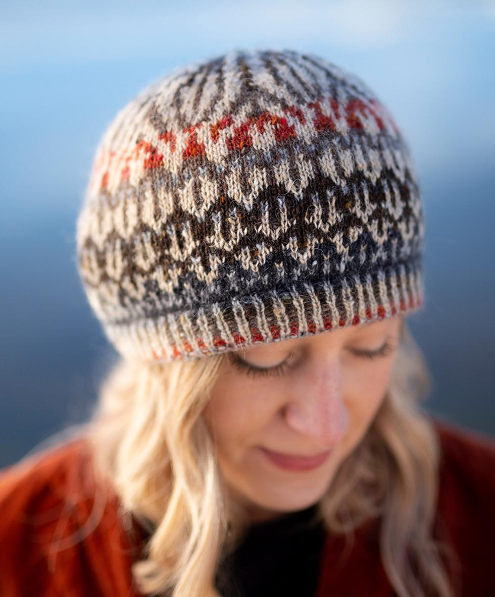 Jane Hunter Models Featherheid - a stranded colourwork hat design based on duck plumage; the background is blue with lochs and skylines