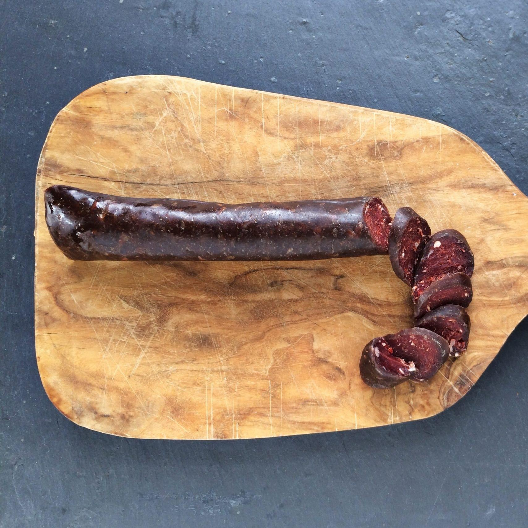 slice venison chorizo on a chopping board