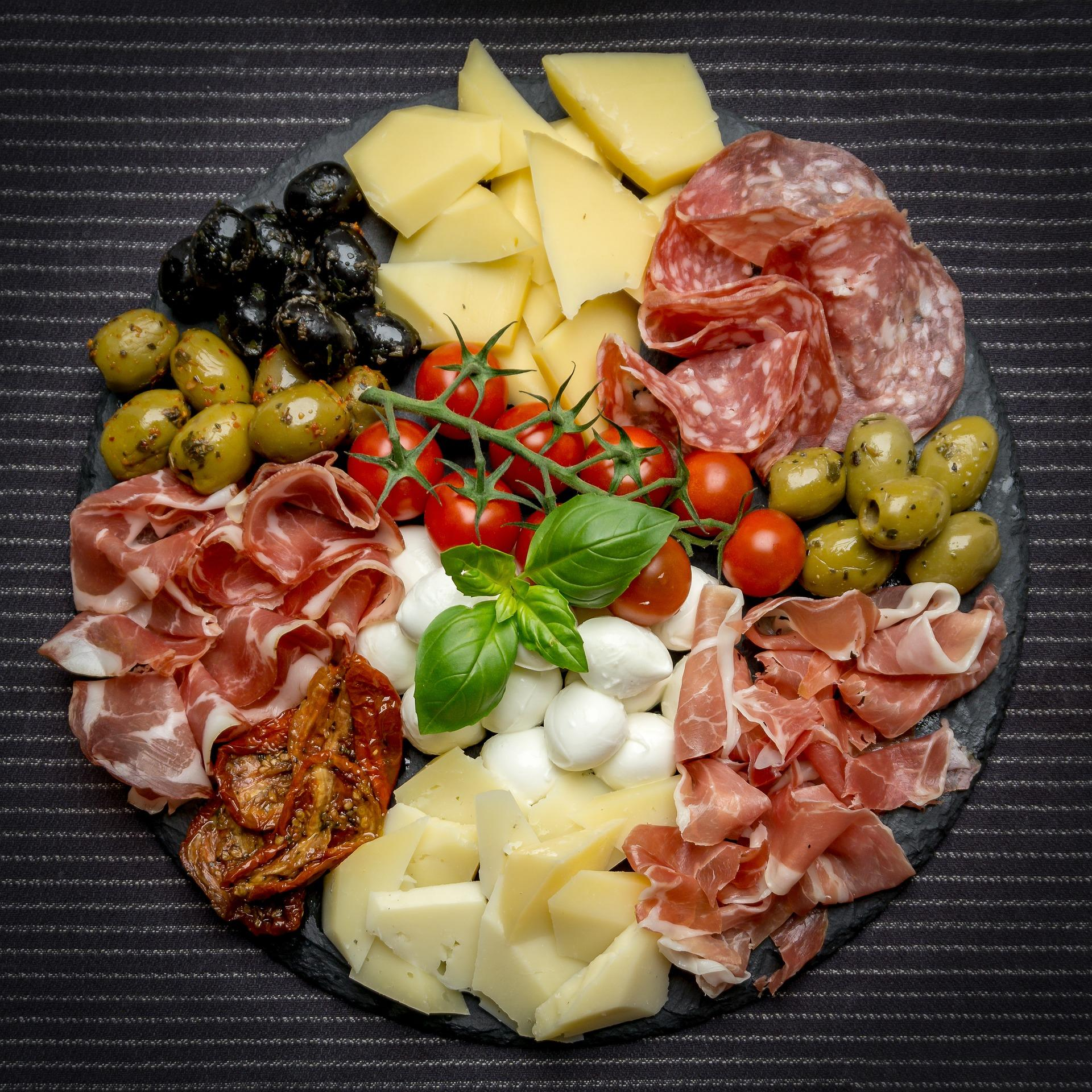 A plate of charcuterie, cheese and olives